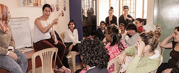 Viele Frauen sitzen in einem Zimmer und werden von einer Lehrerin unterrichtet.